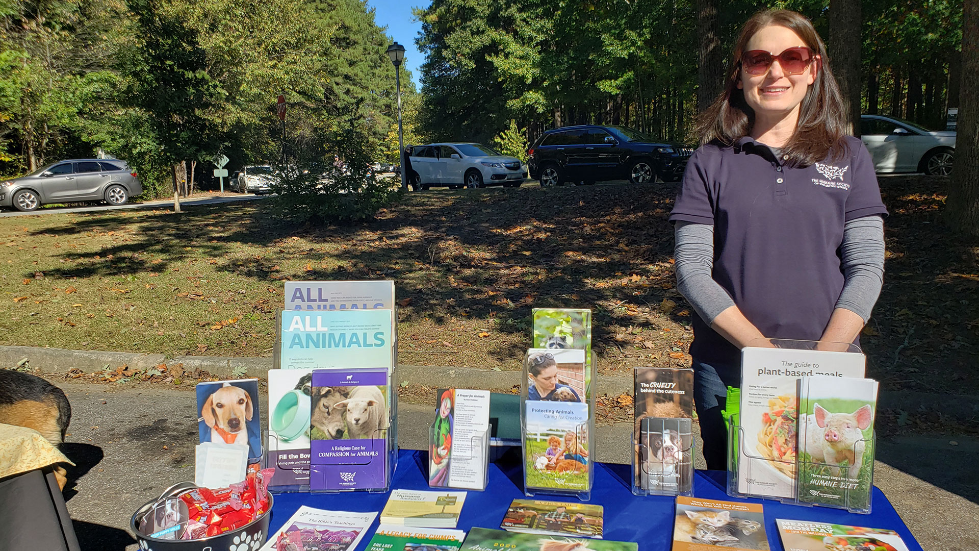 Lisa, a volunteer, stands at a table with animal welfare materials
